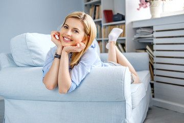 Portrait of blond female lying on a couch.