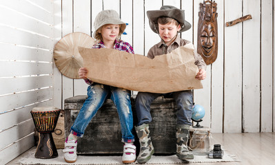 two little tourists study map sitting on big old chest