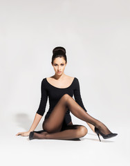 Beautiful, young woman in hosiery sitting on the floor