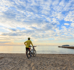 Cyclist with bicycle at the sunrise beach