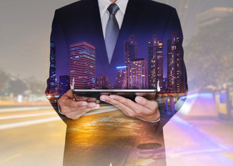 Double exposure of business man hand hold tablet, urban, cicty and street at night as technology and communication concept.
