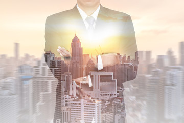 Double exposure of business man arms crossed, cityscape and sunset  as vision of leader concept.