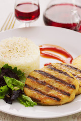 grilled hamburger with rice, salad and chips on plate with glass red wine