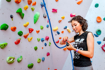 Portrait of beautiful woman rock climber belaying another climber with rope. Indoors artificial climbing wall and equipment.