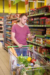 Young man using mobile phone in supermarket