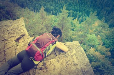 A tourist on the precipice with mountains in the background in vintage style. Young woman on the precipice in Slovak Paradise National Park.