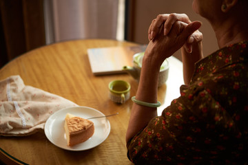 Lonely senior woman with a piece of cake sitting at table