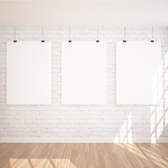 3 Hanging Poster Mock UP In Contemporary Exhibition Interior Space With Floor Lamp. White bricks and wooden floor planks. Perfect Background To Present Your Designs And Photos.