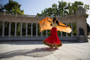 Young beautiful traditional indian woman dancing outdoors