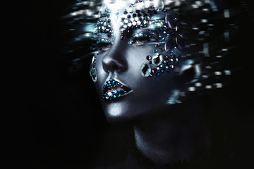 Young beautiful girl in black makeup with rhinestone, dark background, motion effect