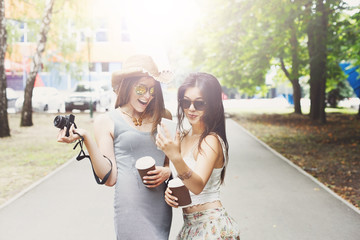 Outdoor portrait of three friends taking photos with a smartphone