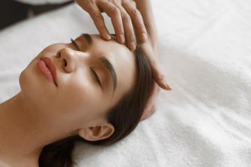 Spa Massage. Beautiful Woman Getting Facial Beauty Treatment
