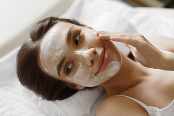 Face Skin Care. Beautiful Woman With Facial Cosmetic Mask At Spa