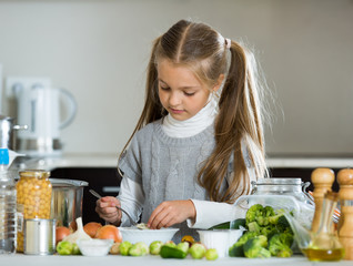 Cute little girl cooking veggies in kitchen