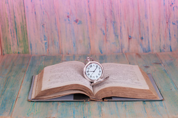 Pocket Watch over Age Book Background ,Time