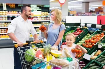 family shopping various fresh vegetables in supermarket
