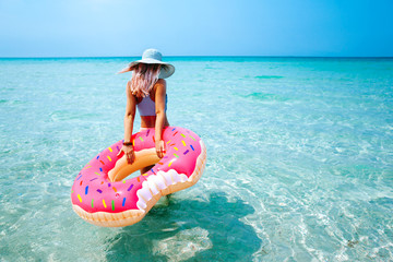 Woman with inflatable ring on beach