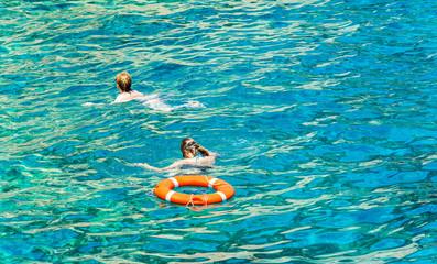 Две женщины плавают в море около спасательного круга