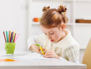 Little girl learns to draw.She uses colored pencils.
