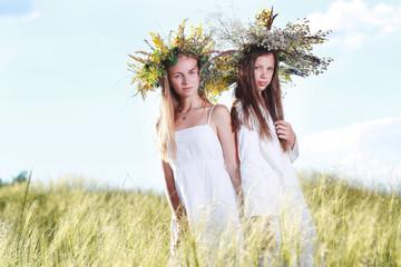 две девушки в венка и белых платьях гуляют в поле