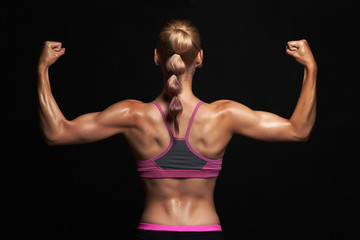 back of athletic girl. gym. muscular fitness woman, trained female body