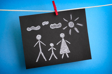 Drawing of a family on black piece of paper