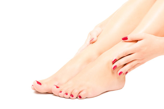Beautiful female foot and hands with red manicure