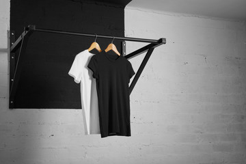 Two basic blank t-shirts - black and white presented on pullbar in crossfit sport center on wooden hangs