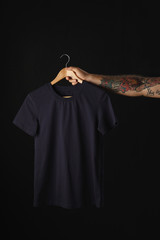 Tattooed hand holds black basic blank t-shirt isolated on black