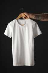 Tattooed hand holds white basic blank t-shirt isolated on black