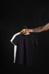 Tattooed hand holds black and white basic blank t-shirts isolated on black