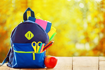 Full School backpack on wooden and autumn nature background