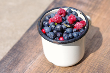 Juicy mature berries of raspberry and bilberry  in an iron mug on a wooden surface.