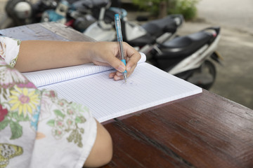 girl holding pen writing on notebook