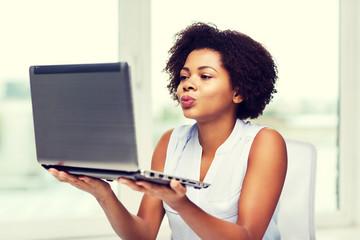 african woman sending kiss to laptop computer