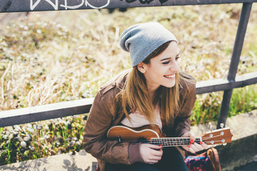 Half length of young beautiful caucasian woman outdoor in the city playing ukulele overlooking smiling - musician, happiness, inspiration concept