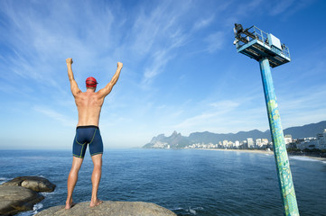Athlete swimmer with swimming cap standing with his arms raised in front of the Rio de Janeiro skyline at Arpoador, Ipanema Beach
