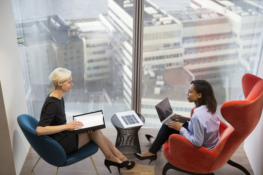 Businesswomen Have Informal Meeting In High Rise Office