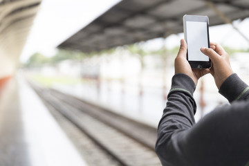 man holding smartphone at train station
