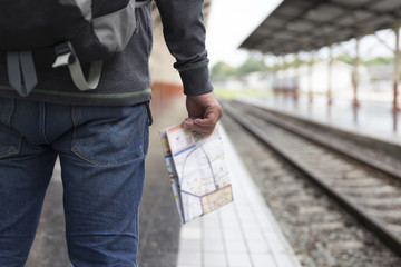 man holding map with backpack at train station