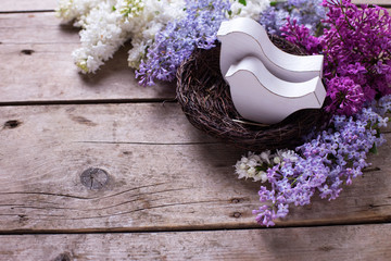 Two decorative birds in nest and  fresh aromatic lilac flowers