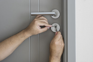 locksmith try to fix a key lock door for open it - can use to display or montage on product