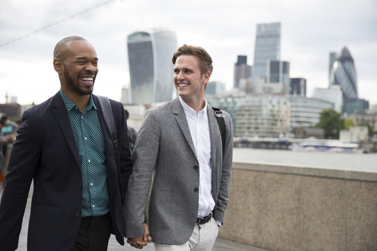 Gay Male Couple Walk To Work With City Skyline In Background