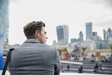 Businessman Looking Out Over London City Skyline