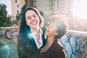 Half length of two multiethnic beautiful young women  having fun chatting and strolling outdoor in city back light - friendship, happiness concept