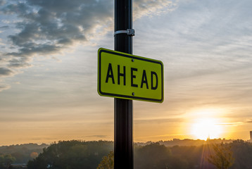 """""""Ahead"""" Street sign with sunrise background. Inspirational image. Motivational image. Sunrise Sunset cloud background. Beautiful Sky background.Minimal art and design. Morning sun. Artistic background"""