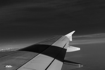 Image of airplane wing in flight. Abstract image of airplane wing isolated. Sky background with point of view from airplane window. Sky and cloud background from airplane view.
