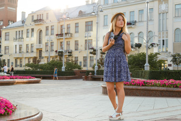 Outdoor summer smiling lifestyle portrait of pretty young woman having fun in the city in Europe in evening with camera