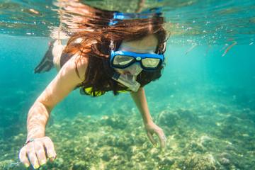 Frau taucht oder schnorchelt in ihrem Urlaub im Tropen Meer Wall mural