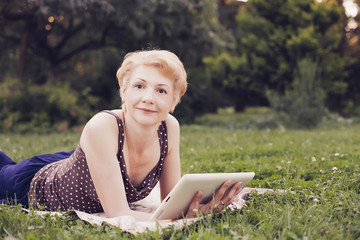 Portrait of middle aged woman using tablet  in the park